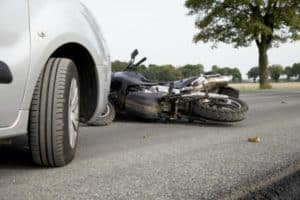 A car has crashed into a motorcycle.