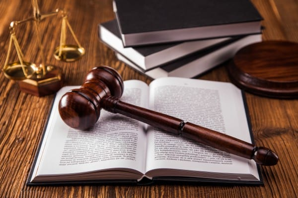 A gavel onto of a law book with a set of legal scales on a desk.