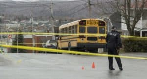 An police officer overlooking the cleanup of a school bus accident.