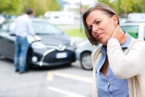 A woman is holding her neck after a car accident.