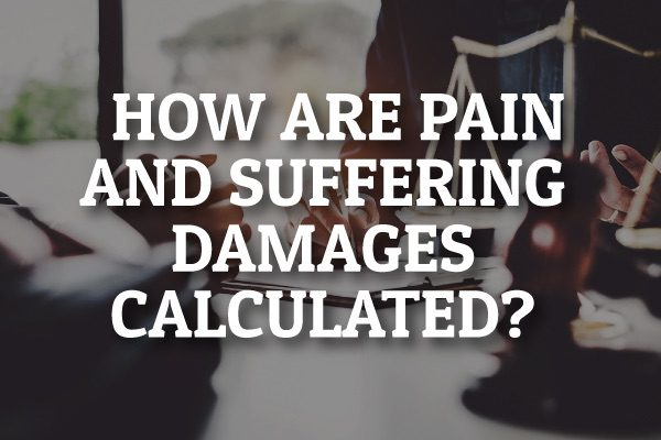 """A lawyer sitting at a desk with the words, """"how are pain and suffering damages calculated?"""""""