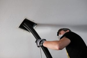 A Technician gets deep into the air ducts to clean years of dust and debris