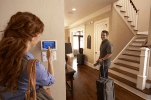 Woman adjusting thermostat as husband walks away with suitcase