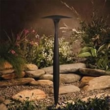 A tall LED light fixture overlooking a garden