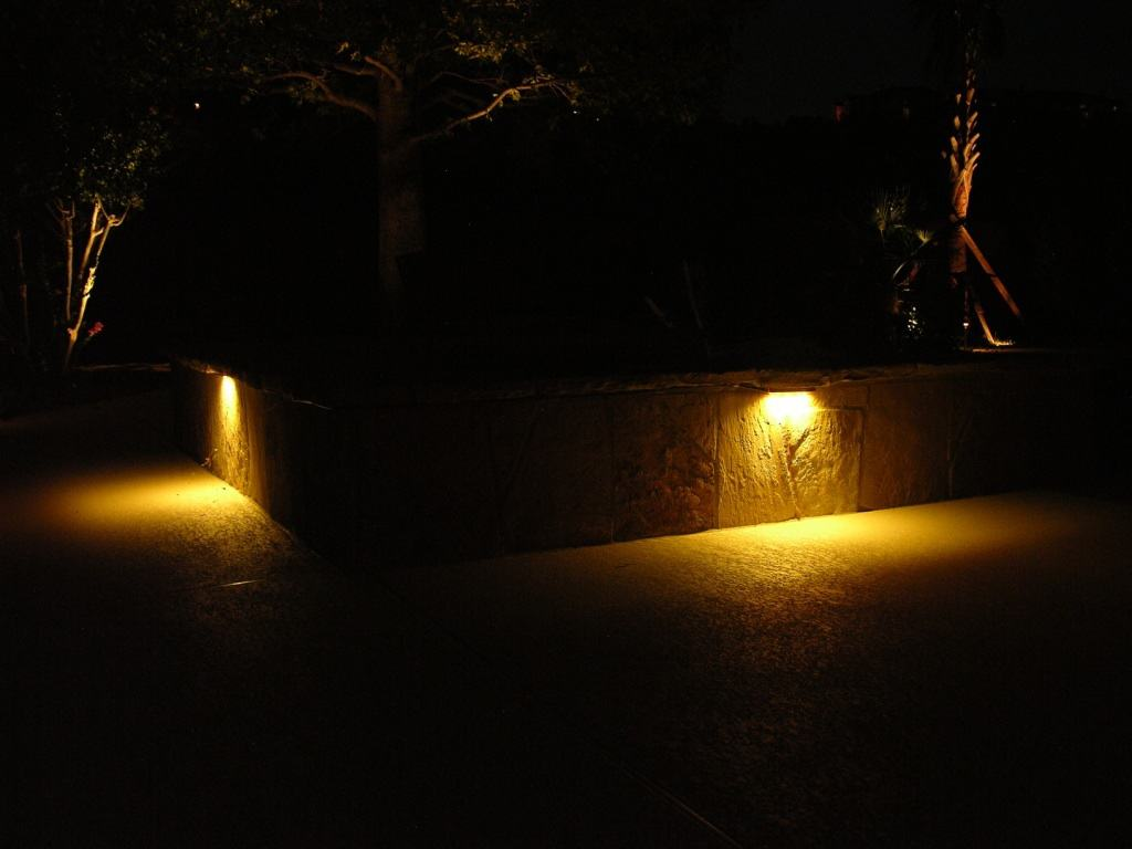 Lighting fixtures on a stone wall light up a pathway
