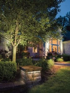 Stone work and landscaping brightly lit in front of a home