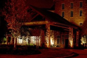 Lights shine up the stone walls of an office building