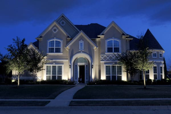 Large two-story home and trees lit up at night