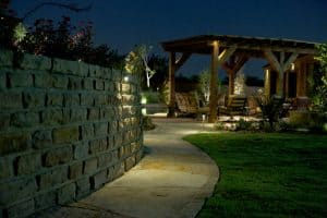 A pathway leading to a pergola is illuminated by LED lighting