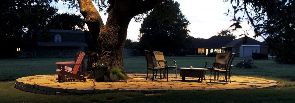 Lighted tree and patio furniture on stone slab in backyard