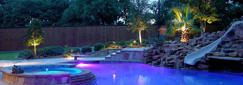 Colorful poolside lighting at dusk beautifies the entire back yard