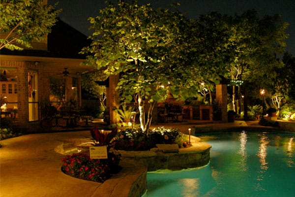 Poolside lights shine up at the landscaping accenting the pool