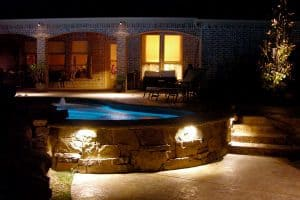 A backyard pool lit up and ready to be enjoyed on a beautiful night