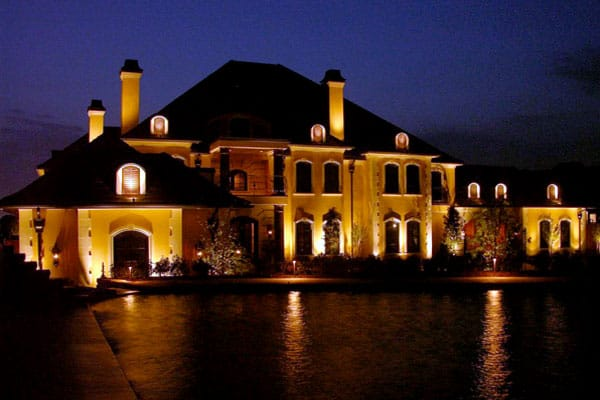 Two-story home with pond in front at night lit up by security lighting