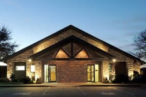 The entrance to a stone clinic building is lit byy security lighting at night