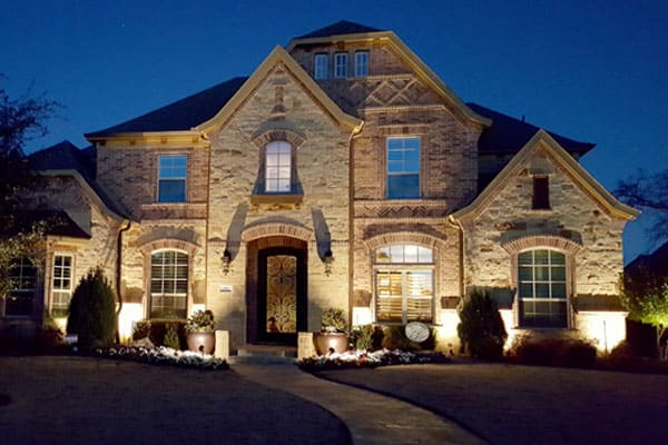 A Dallas Ft Worth area home is illuminated at night by outdoor lighting