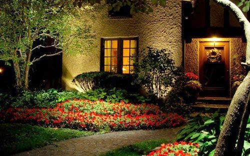 A well lit front yard with porch lights and lights that highlight plants and illuminate the path