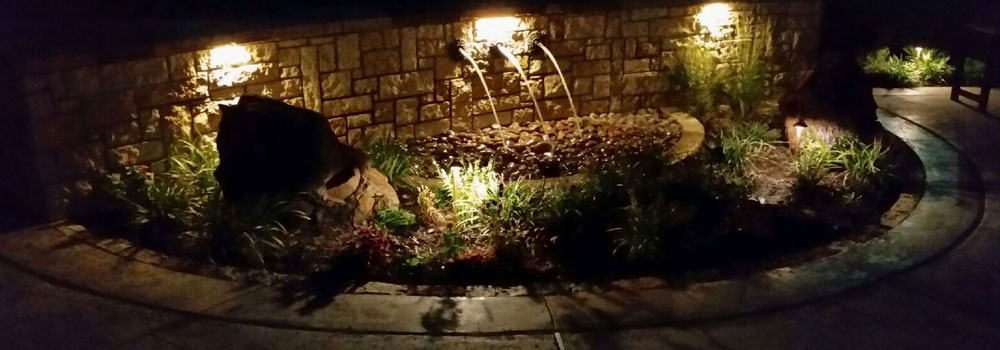 Well-lit water feature with water pouring from stone wall