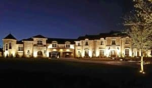 A mansion's exterior is illuminated by well designed outdoor lighting