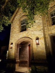 The dramatic stonework of a homes exterior seen by the light of outdoor LED lighting