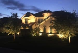 A home is visible at night thanks to outdoor lighting
