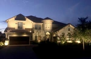 A home's exterior can be seen at night by the light of outdoor LEDs