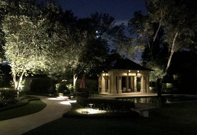A beautiful back yard with a gazebo seen at night by outdoor lighting