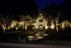 Landscaping features are visible at night by LED lighting