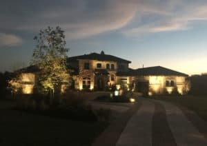A home's exterior seen lit up by well designed landscape lighting
