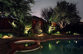 A swimming pool is professionally lit up at night