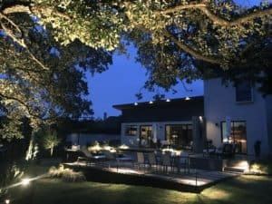 A modern home's backyard is visible at night by outdoor lighting