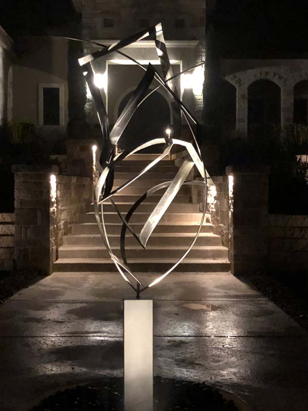 Image of a metal sculpture being lit with outdoor led lighting