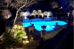A beautifully lit pool with bubblers inside and plants all around