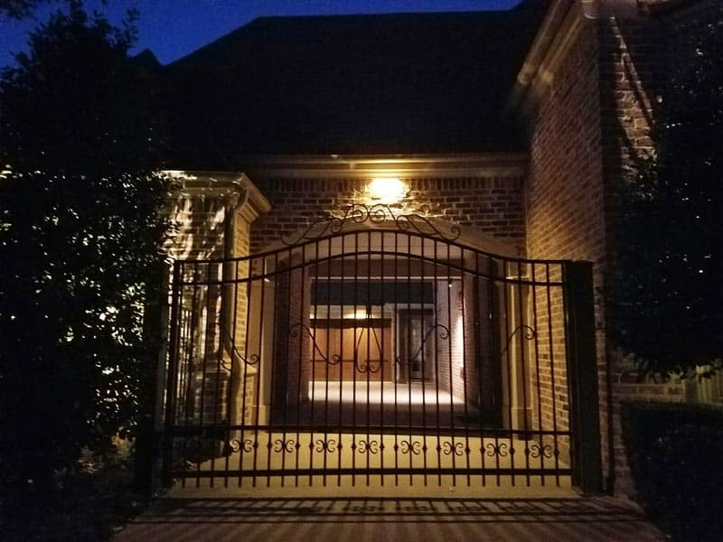 A porch with a soffit security light and a wrought iron fence in front of it