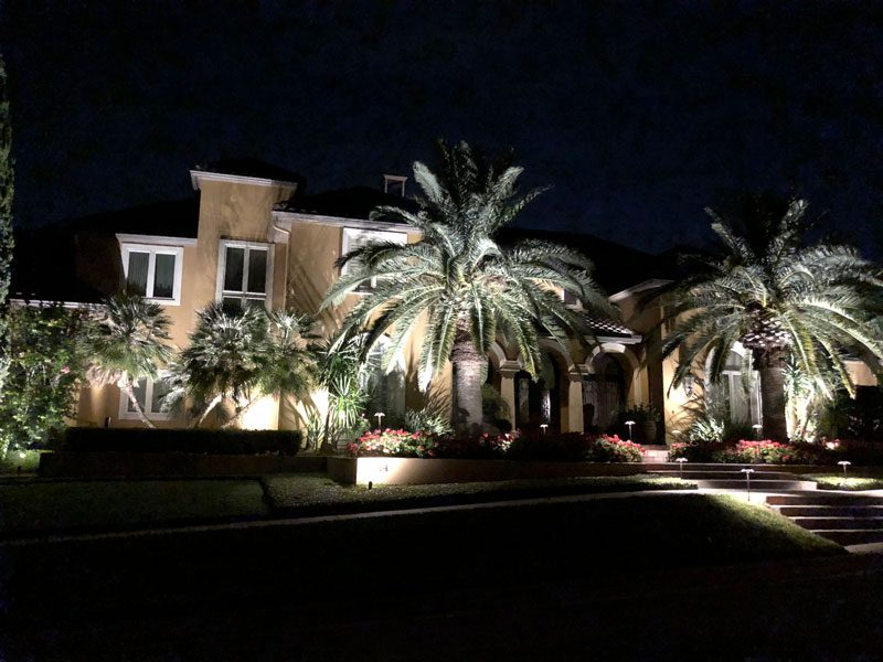 Well-lit flower bed and palm trees in front of a beautiful Spanish style home
