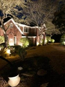 front yard of a home lit up by exterior lighting