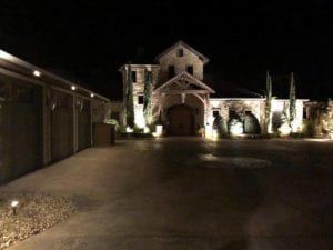exterior lighting lights up a beautiful home and driveway
