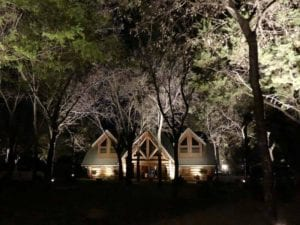 a cabin in the wood lit up with exterior lighting