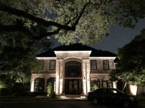 beautiful red brick home with outdoor lighting
