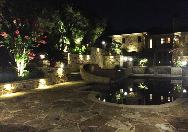 A gorgeous outdoor lighting set up around a pool.