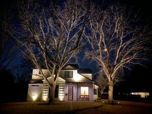 white wooden home lit up with landscape lighting