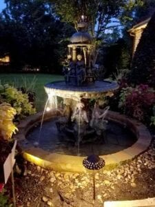 water fountain in a garden lit up with outdoor lighting