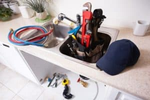 A plumber's tools and assorted hardware in a kitchen sink
