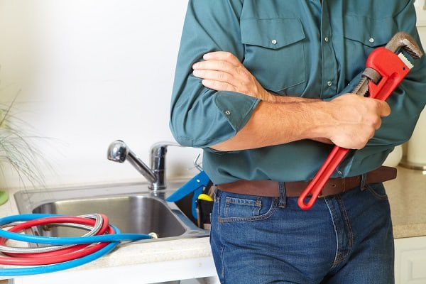 Plumber in a kitchen fixing a stopped up sink drain