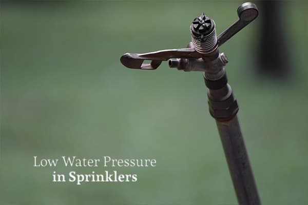 A close up of a water sprinkler head with words to the left that read, low water pressure in sprinklers