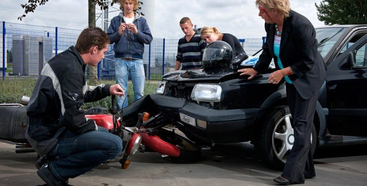 A rider looks at the damage to his motorcycle after an accident