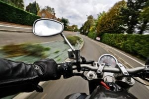 A motorcycle driving down the road from the rider's point of view
