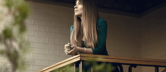 A woman leans on the railing of her balcony