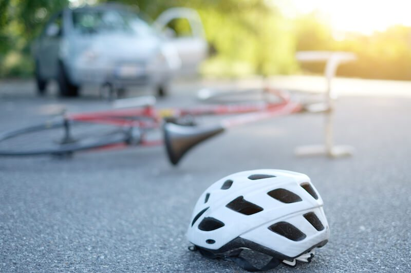 A bicycle and helmet on the street after being hit by a car