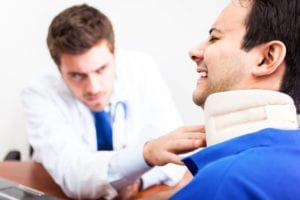 A doctor checks the alignment of a brace holding a victim's neck still